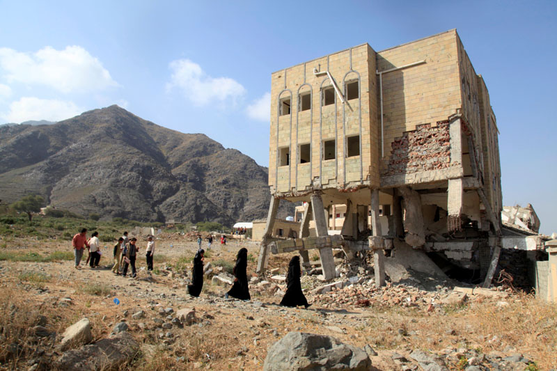 People walk past a school damaged during the ongoing war in Taiz, Yemen, December 18, 2018. Photo: Reuters