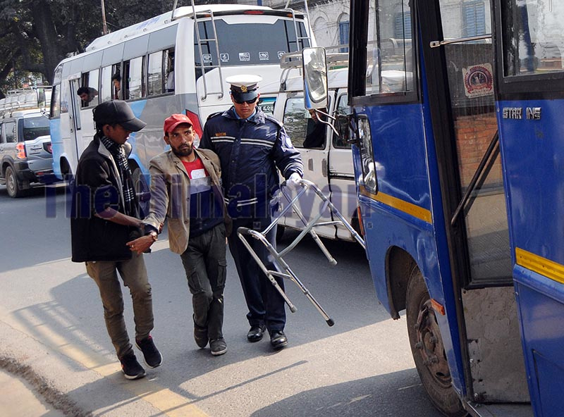 A traffic policeman, aided by a civilian, helping a differently-abled person cross a road, in Kathmandu, on Tuesday. Photo: Balkrishna Thapa Chhetri/ THT