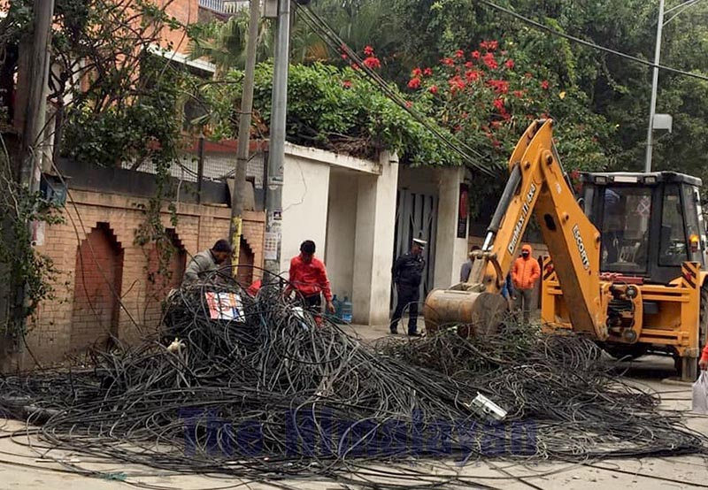 An excavator being used to dump the dangling wires that were cut off from poles in the tourist hub of Thamel, Kathmandu, on Wednesday, December 18, 2019. Photo: THT