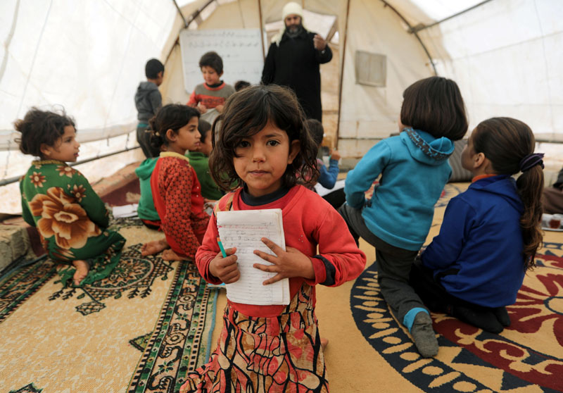 A student holds a notebook as she sits at a makeshift school in a tent in Azaz, Syria January 12, 2020. Photo: Reuters