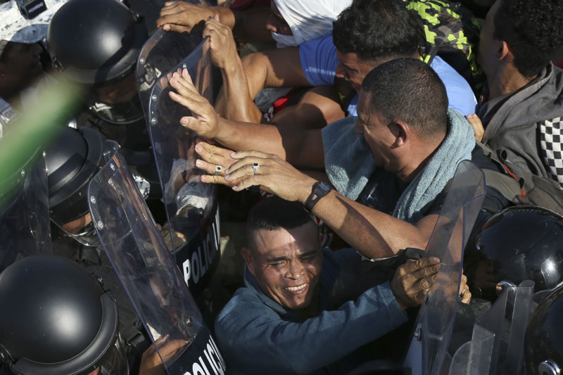 Migrants scuffle with Mexican National Guardsmen at the border crossing between Guatemala and Mexico in Tecun Uman, Guatemala, Saturday, Jan. 18, 2020. Photo: AP