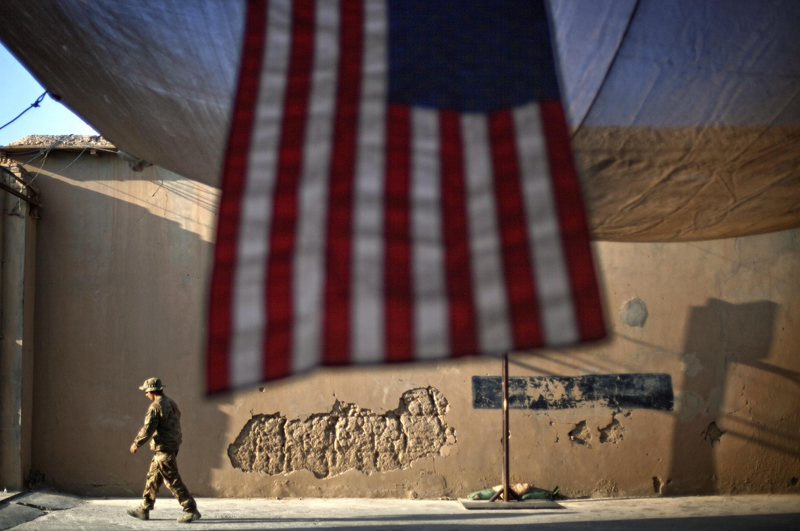 A US Army soldier with the 25th Infantry Division, 3rd Brigade Combat Team, 2nd Battalion 27th Infantry Regiment walks past an American Flag hanging in preparation for a ceremony commemorating the tenth anniversary of the 9/11 attacks, Sept 11, 2011 at Forward Operating Base Bostick in Kunar province, Afghanistan, Sept 11, 2011. Photo: AP/File