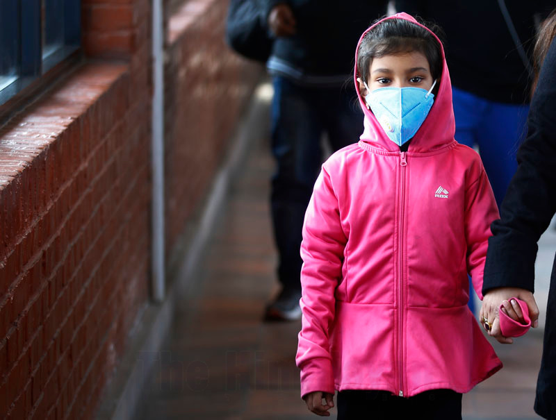 A girl wears mask as a protective measure upon her arrival at Tribhuvan International Airport, in Kathmandu, on Tuesday, January 28, 2020. Photo: Skanda Gautam/THT
