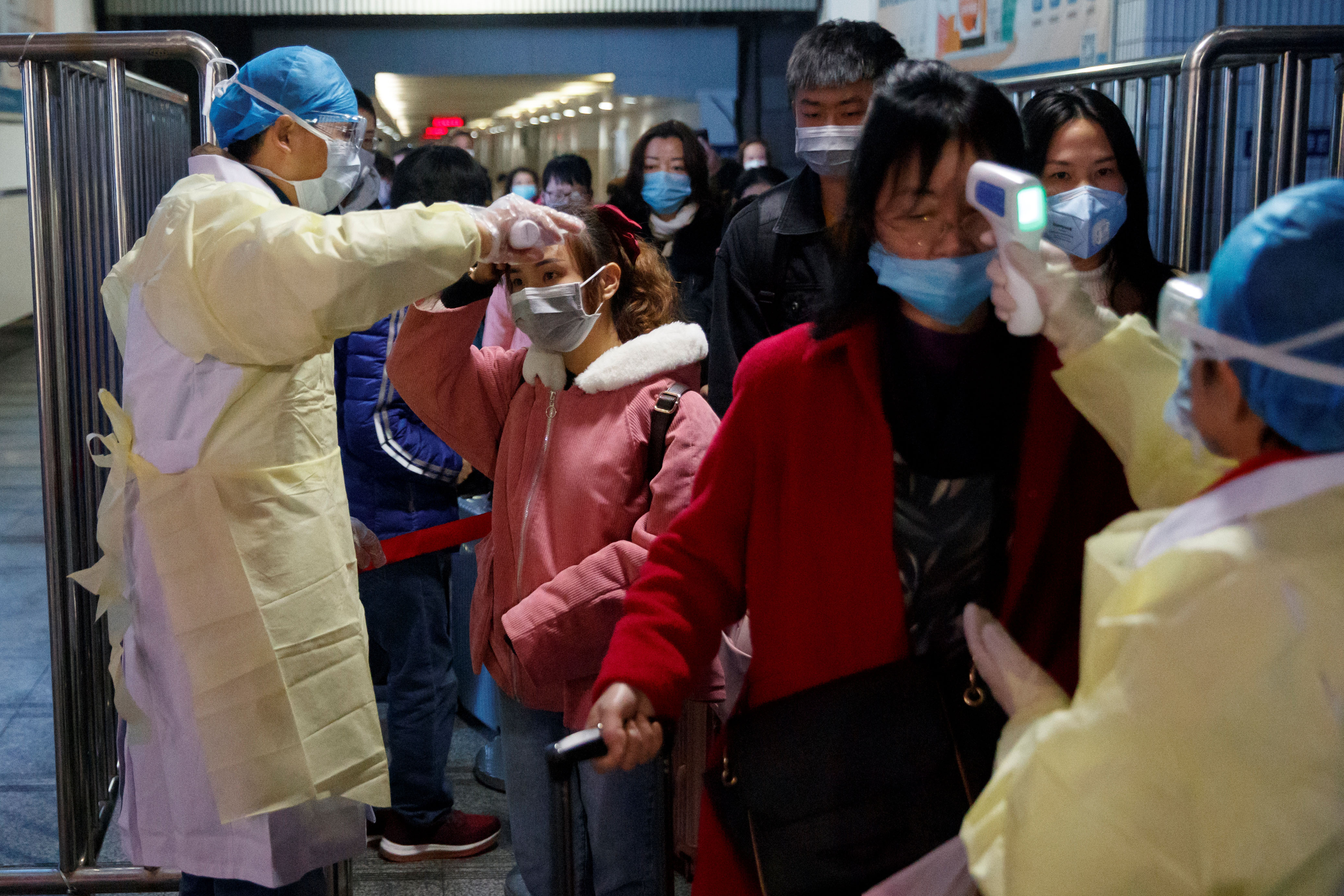 Medical workers take the temperature of passengers after they got off the train in Jiujiang, Jiangxi province, China, as the country is hit by an outbreak of a new coronavirus, January 29, 2020. Photo: Reuters