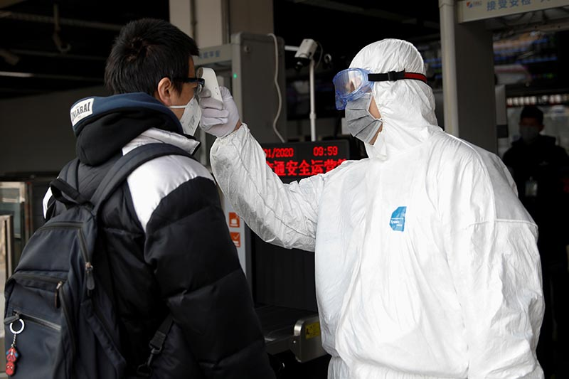 A worker in protective suit uses a thermometer to check the temperature of a man while he enters the Xizhimen subway station, as the country is hit by an outbreak of the new coronavirus, in Beijing, China January 27, 2020. Photo: Reuters