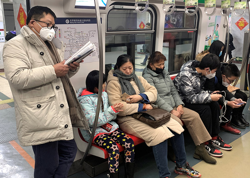 A man wearing a mask reads on the subway in Beijing, China, on January 21, 2020. Photo: Reuters