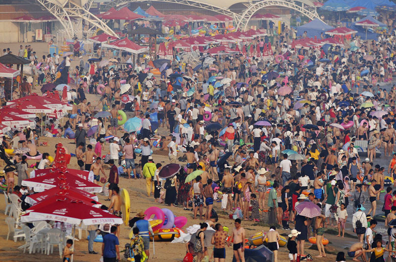 In this July 12, 2017, file photo, visitors flock to a beach in Qingdao in eastern China's Shandong Province. China's population crept past 1.4 billion in 2019 for the first time, even as the birthrate continues to fall. Photo: AP