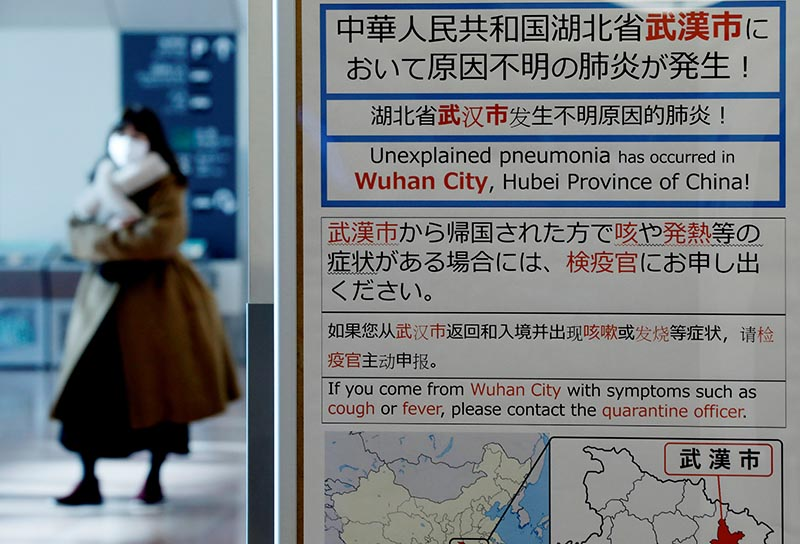 A woman wearing a mask walks past a quarantine notice about the outbreak of coronavirus in Wuhan, China at an arrival hall of Haneda airport in Tokyo, Japan, January 20, 2020. Photo: Reuters