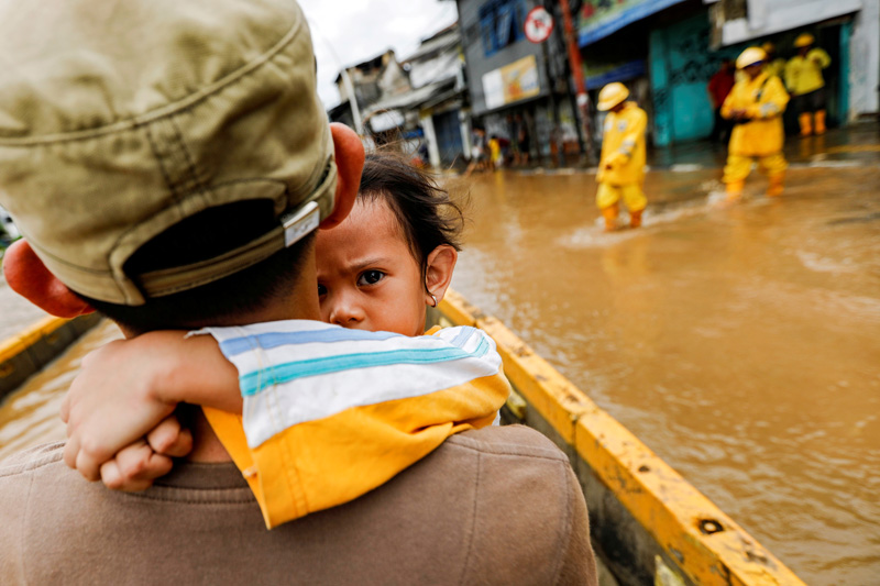 A girl is carried by her father across floodwaters in the Jatinegara area after heavy rains in Jakarta, Indonesia, January 2, 2020. Photo: Reuters