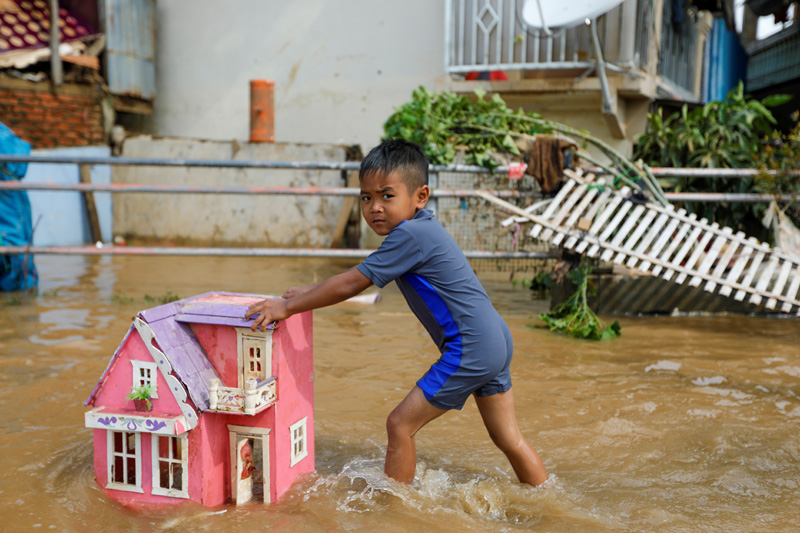 A boy pushes a toy house as he plays in floodwaters after heavy rains in Jakarta, Indonesia, January 2, 2020. Photo: Reuters