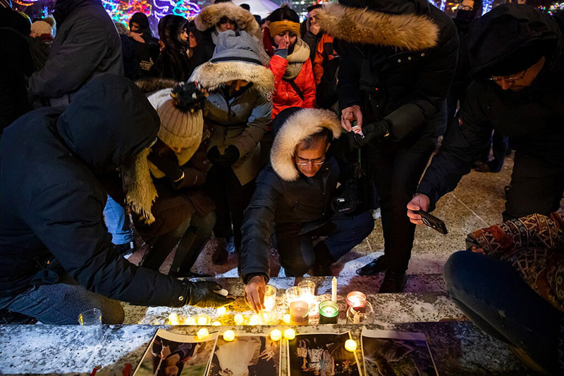 Mourners place candles and photographs outside the Alberta Legislature Building in Edmonton, Alberta, Wednesday, January 8, 2020, during a vigil for those killed after a Ukrainian passenger jet crashed, killing at least 63 Canadians, just minutes after taking off from Iran's capital. Photo: The Canadian Press via AP