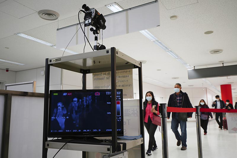 Travelers from China's Wuhan and other cities go through body temperature scanners at Narita airport in Narita, near Tokyo, on January 23, 2020. Japan said Monday it is preparing to send chartered flights to China to evacuate Japanese citizens out of Wuhan, the epicenter of as the new coronavirus outbreak, as the death toll and the number of patients rapidly increase and transportation in and out of the city is cut off. Photo: AP