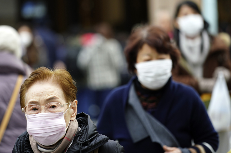 Pedestrians wear protective masks as they walk through a shopping district in Tokyo Thursday, Jan. 16, 2020. Japan's government said Thursday a man treated for pneumonia after returning from China has tested positive for the new coronavirus identified as a possible cause of an outbreak in the Chinese city of Wuhan. Photo: AP
