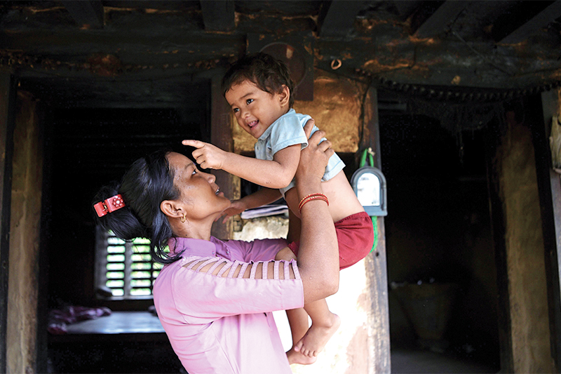 This file photo shows Asha Charti Karki, who got married at the age of 16 and mentors young girls on the importance of education, playing with her daughter in their home in Barahataal of Surkhet, 520km west of Kathmandu. Photo: AFP