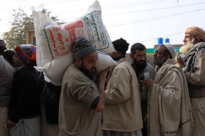 A man carries sacks of flour on his shoulder, while others stand in queue to purchase from a truck along a road in Peshawar, Pakistan January 20, 2020. Photo: Reuters