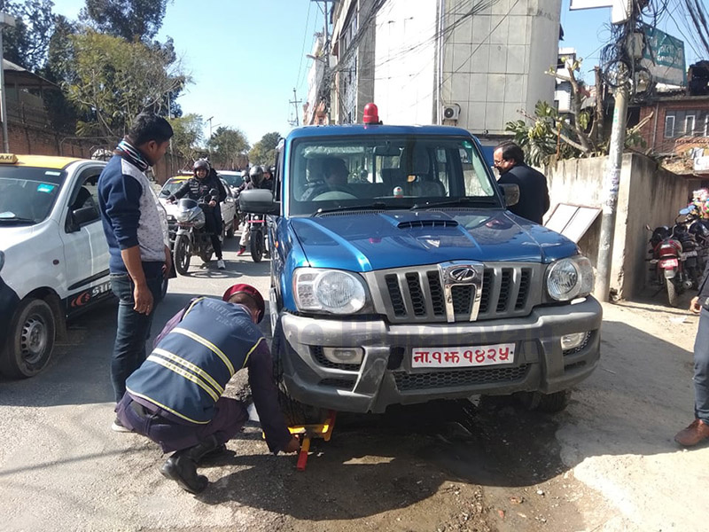 In this picture, a traffic police personnel is seen clamping the wheel of a Nepal Police vehicle (Na 1 Jha 1425) for breaching traffic rules, in Anamnagar, Kathmandu, on Monday, January 20, 2020. Photo: Sujan Dhungana/THT