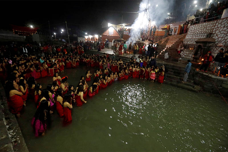 Devotees offer prayers before taking a holy bath in the Sali River during the Swasthani Brata Katha festival early morning in Kathmandu, on Friday, January 10, 2020. Photo: Reuters