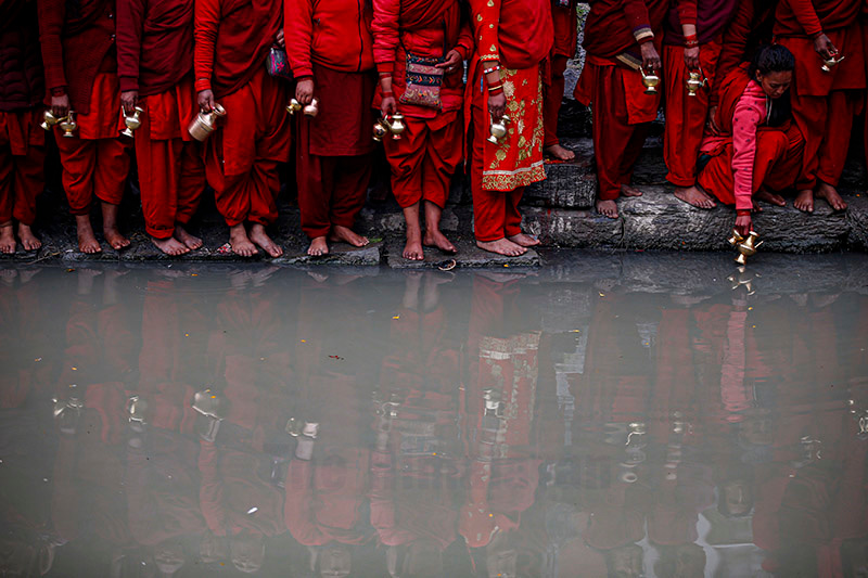 Women stand on the banks of Bagmati river to collect holy water during the month-long Swasthani Bratakatha festival, dedicated to Goddess Shree Swasthani, at Pashupathinath Temple, in Kathmandu, on Friday, January 24, 2020. Photo: Skanda Gautam/THT