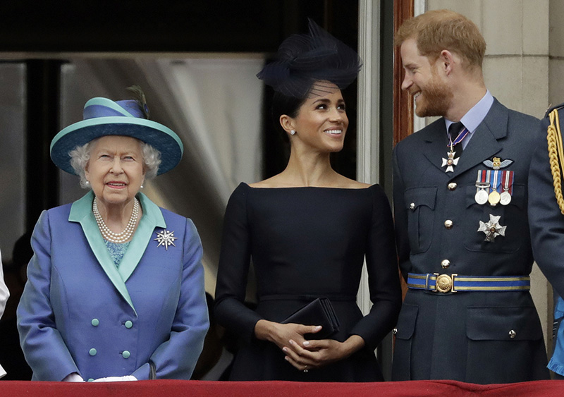 In this Tuesday, July 10, 2018 file photo Britain's Queen Elizabeth II, and Meghan the Duchess of Sussex and Prince Harry watch a flypast of Royal Air Force aircraft pass over Buckingham Palace in London. Photo: AP