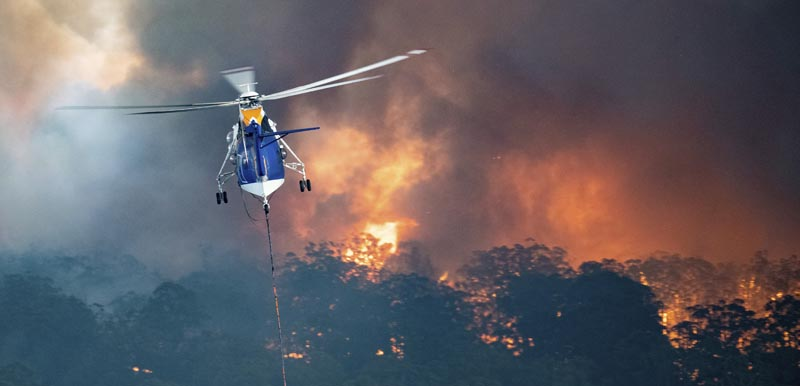 In this Monday, December 30, 2019 photo provided by State Government of Victoria, a helicopter tackles a wildfire in East Gippsland, Victoria state, Australia. Photo: State Government of Victoria via AP