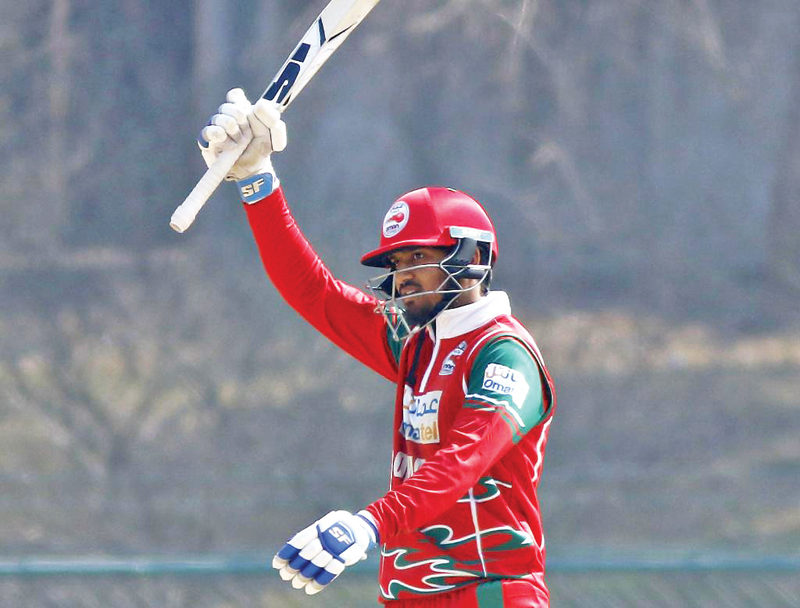 Aqib Ilyas of Oman raises his bat as he celebrates after scoring a century against the United States during their ICC Cricket World Cup League2 match at the TU Stadium in Kathmandu on Tuesday. Photo: ICC