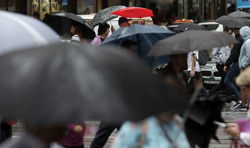 People shelter under a jumble of umbrellas as rain falls Friday, Feb 7, 2020, while the Bureau of Meteorology issued severe weather warning along the New South Wales state coast. Photo: AP