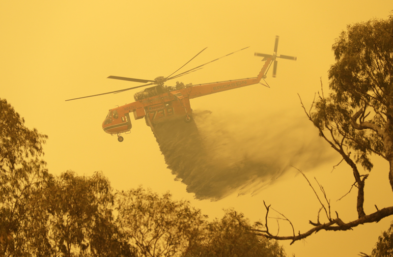 A helicopter drops water on a fire near Bumbalong, south of the Australian capital, Canberra, Saturday, Feb 1, 2020. Photo: AP