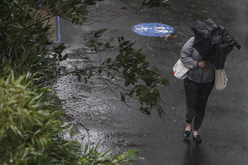 A pedestrian braves strong wind and rain in Sydney, New South Wales, Australia, February 9, 2020. Photo: Reuters