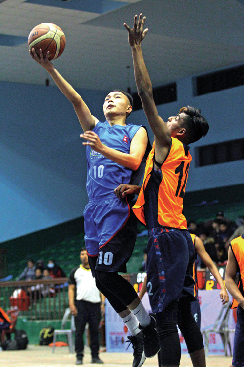 Pemba Sherpa (left) of Times International College jumps to score against Nirajan Yadav of White House College during the IIMS 5th National U-18 Basketball Championship at National Sports Council covered hall, Tripureshwor in Kathmandu on Friday. Photo: Udipt Singh Chhetry/THT