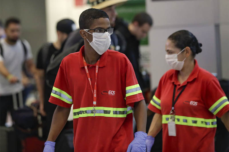 Airport employees wear masks as a precaution against the spread of the new coronavirus COVID-19 as they work at the Sao Paulo International Airport in Sao Paulo, Brazil, Wednesday, Feb. 26, 2020. Photo: AP