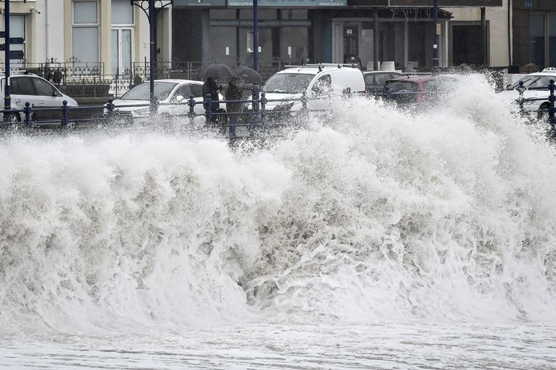 People watch waves pound against the harbour wall at Porthcawl in Wales, as Storm Dennis sweeps across the country, Saturday Feb 15, 2020. Photo: Ben Birchall/PA via AP