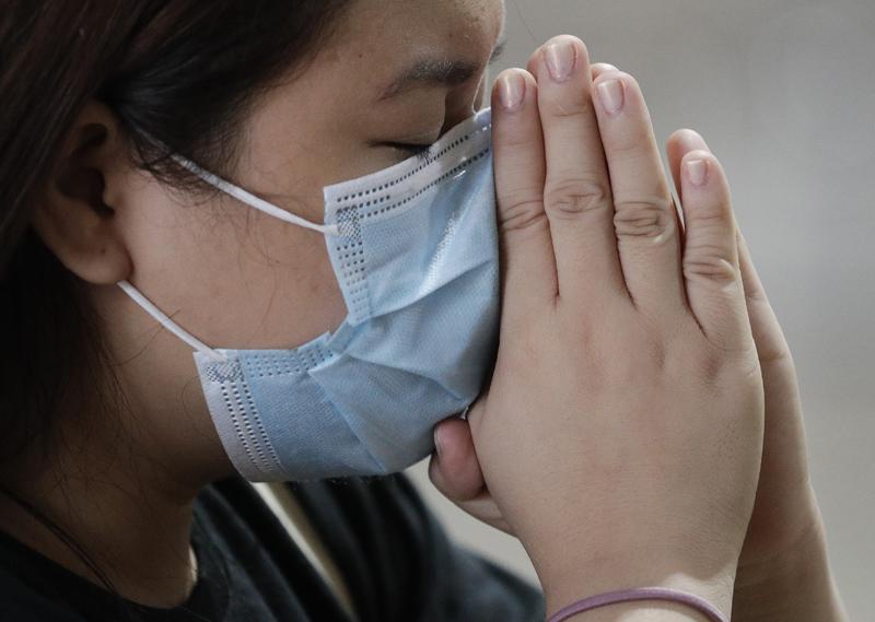 A Catholic woman wearing a face mask prays during a mass at the Minor Basilica of San Lorenzo Ruiz in Manila's Chinatown, Philippines,  Feb 10, 2020. Photo: AP