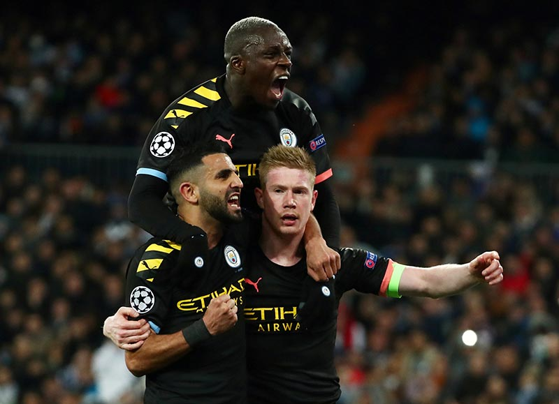 Manchester City's Kevin De Bruyne celebrates scoring their second goal with Riyad Mahrez and Benjamin Mendy during the Champions League Round of 16 First Leg match between Real Madrid and Manchester City, at Santiago Bernabeu, in Madrid, Spain, on February 26, 2020. Photo: Reuters