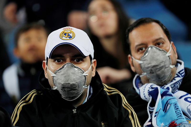 FILE - Real Madrid fans wearing face masks amid concern of the coronavirus inside the stadium before the Champions League Round of 16 First Leg match between Real Madrid and Manchester City, at Santiago Bernabeu, in Madrid, Spain, on February 26, 2020. Photo: Reuters