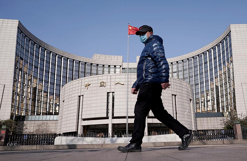 FILE PHOTO: A man wearing a mask walks past the headquarters of the People's Bank of China, the central bank, in Beijing, China, as the country is hit by an outbreak of the new coronavirus, February 3, 2020.  Photo: Reuters