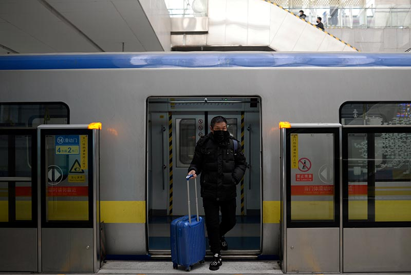 FILE - A man wearing a face mask walks out of the subway with a suitcase in the morning after the extended Lunar New Year holiday caused by the novel coronavirus outbreak, at the Xierqi subway station, in Beijing, China February 10, 2020. Photo: Reuters