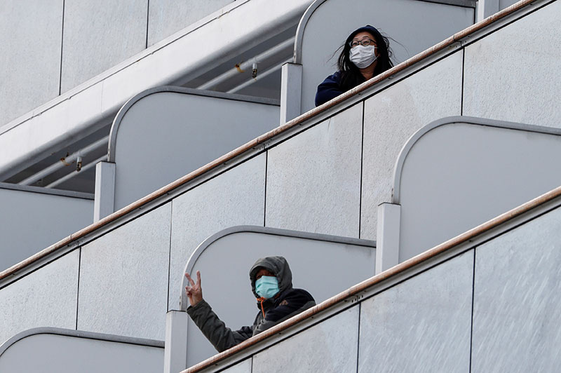 Passengers wearing face masks react as the cruise ship Diamond Princess, where 10 people on the ship had tested positive for coronavirus yesterday, arrives at Daikoku Pier Cruise Terminal in Yokohama, south of Tokyo, Japan February 6, 2020. Photo: Reuters