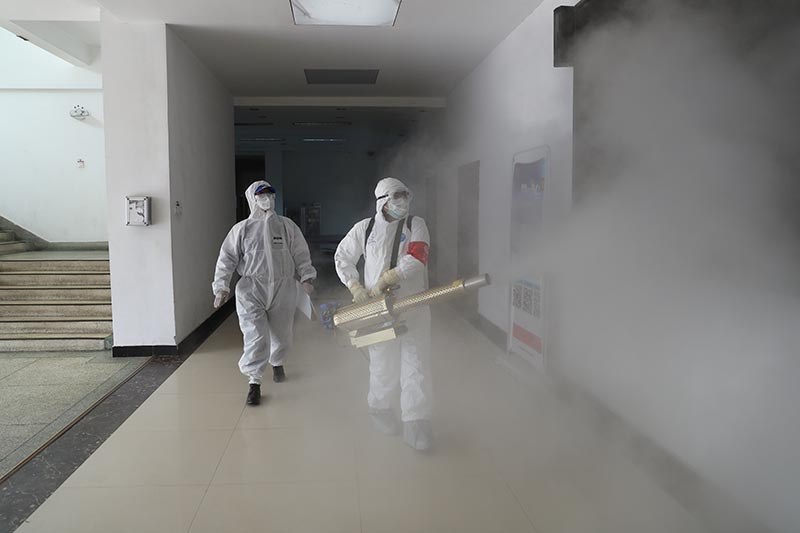 Volunteers in protective suits disinfect a residential compound in Wuhan, the epicentre of the novel coronavirus outbreak, in Hubei province, China February 22, 2020. Photo: China Daily via Reuters