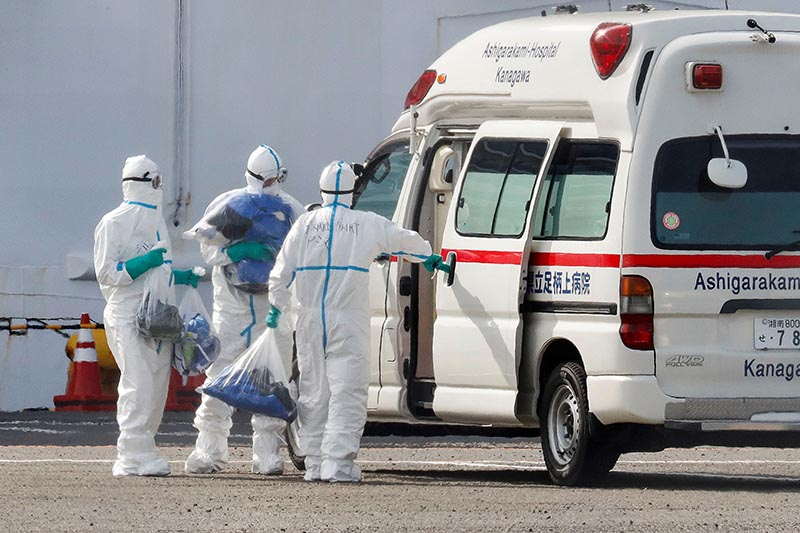 Officers wearing protective suits carry plastic bags next to an ambulance, near the cruise ship Diamond Princess, where 10 more people were tested positive for coronavirus on Thursday, at Daikoku Pier Cruise Terminal in Yokohama, south of Tokyo, Japan February 7, 2020. Photo: Reuters