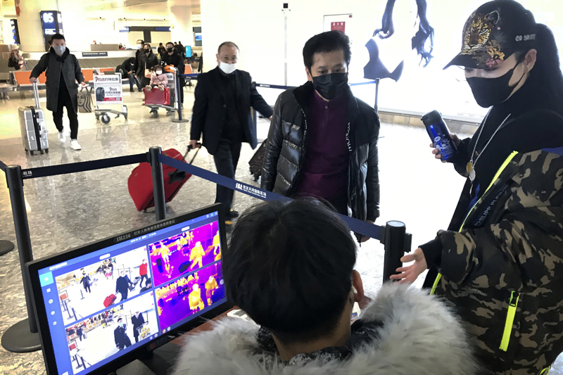 Travelers pass through a health screening checkpoint at Wuhan Tianhe International Airport in Wuhan in southern China's Hubei province, Jan 21, 2020. Photo: AP/File