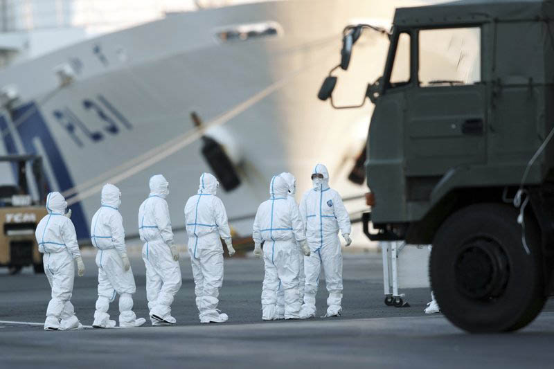 Officials with protective suites prepare work around the quarantined cruise ship Diamond Princess in the Yokohama Port Monday, Feb. 10, 2020, Yokohama, Japan. Photo: AP