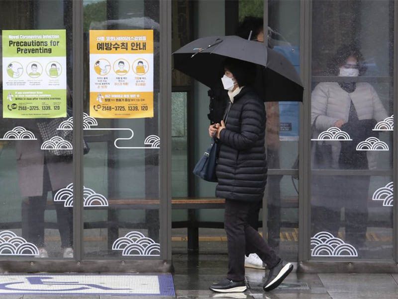 A woman wearing face mask passes by posters about precautions against new coronavirus at a bus station in Seoul, South Korea, Tuesday, Feb. 25, 2020. China and South Korea on Tuesday reported more cases of a new viral illness that has been concentrated in North Asia but is causing global worry as clusters grow in the Middle East and Europe. Photo: AP
