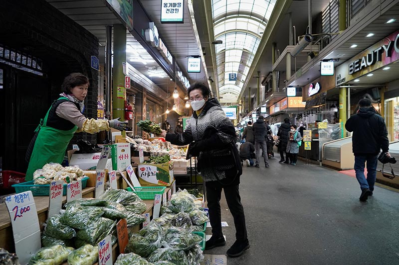 A woman wearing a mask to prevent contacting the coronavirus shops at a traditional market in Seoul, South Korea, on February 24, 2020.  Photo: Reuters