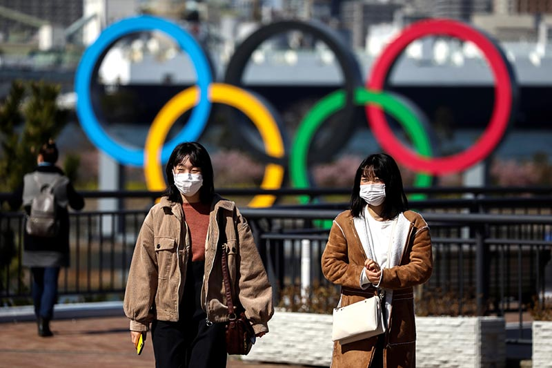 People wearing protective face masks, following an outbreak of the coronavirus, are seen in front of the Giant Olympic rings at the waterfront area at Odaiba Marine Park in Tokyo, Japan, on February 27, 2020. Photo: Reuters