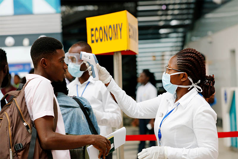 FILE PHOTO: A health worker checks the temperature of a traveller as part of the coronavirus screening procedure at the Kotoka International Airport in Accra, Ghana January 30, 2020. Photo: Reuters