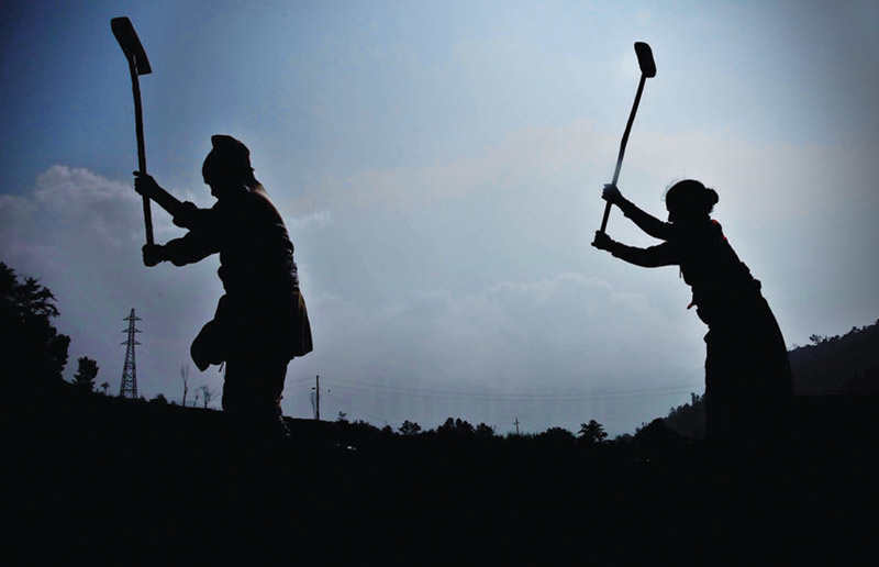 Farmers silhouetted against the sky as they work in a field on the outskirts of Kathmandu, on Friday. Photo: Skanda Gautam/THT