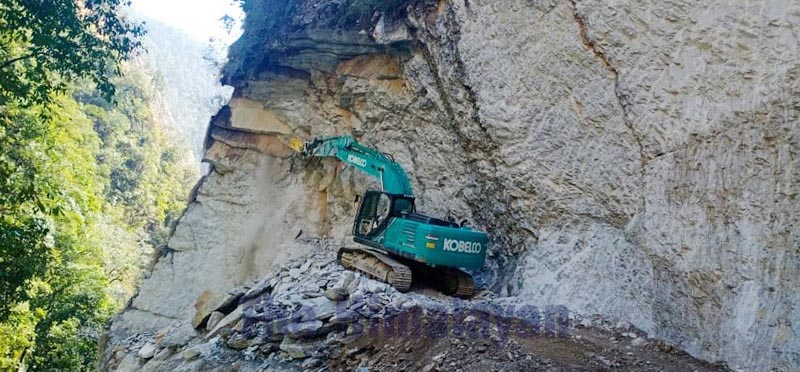 An excavator being used to expand road along the Ghatamuna-Kalchhe section at Kalchhebhir in Gaumul Rural Municipality, Bajura, on Monday, February 24, 2020. Photo: THT