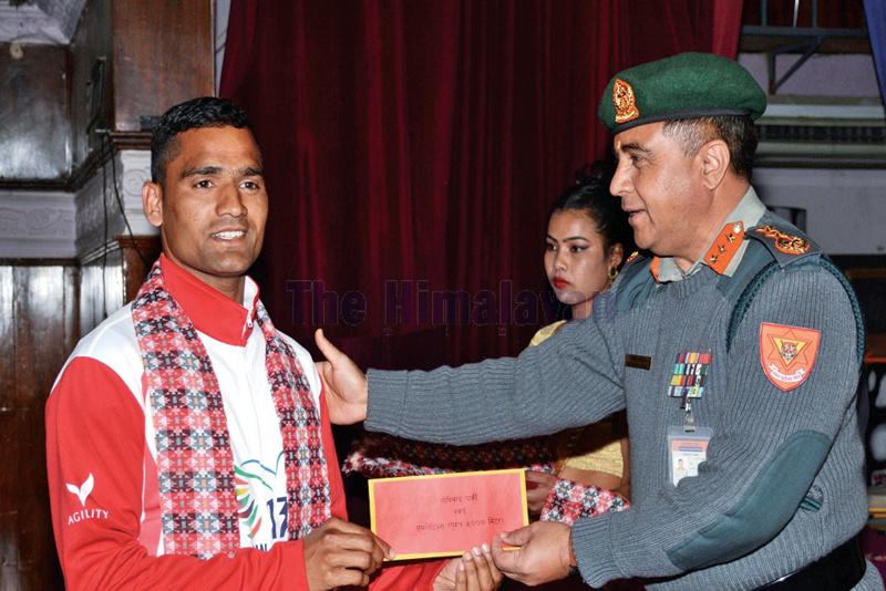 The 13th South Asian Games 5,000m race gold medal winner Gopi Chandra Parki receiving rewards from APF Inspector General Shailendra Khanal at a felicitation programme in Kathmandu on Sunday. Photo: THT