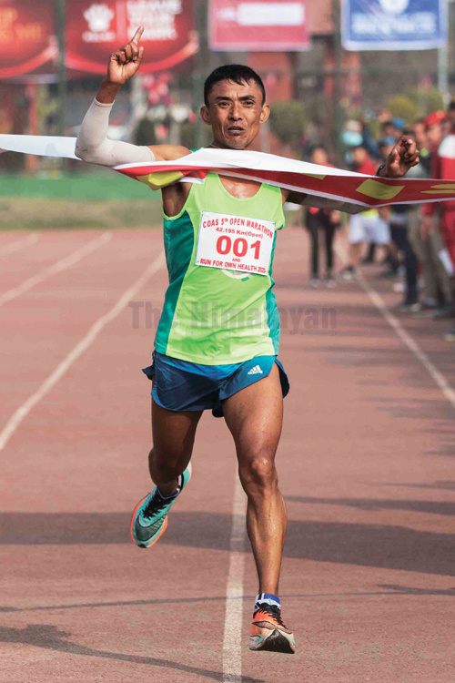 Hom Lal Shrestha of Tribhuvan Army Club gestures after crossing finish line of the CoAS 5th Open Marathon at Army grounds Bhadrakali in Kathmandu on Saturday. Photo: Udipt Singh Chhetry/THT
