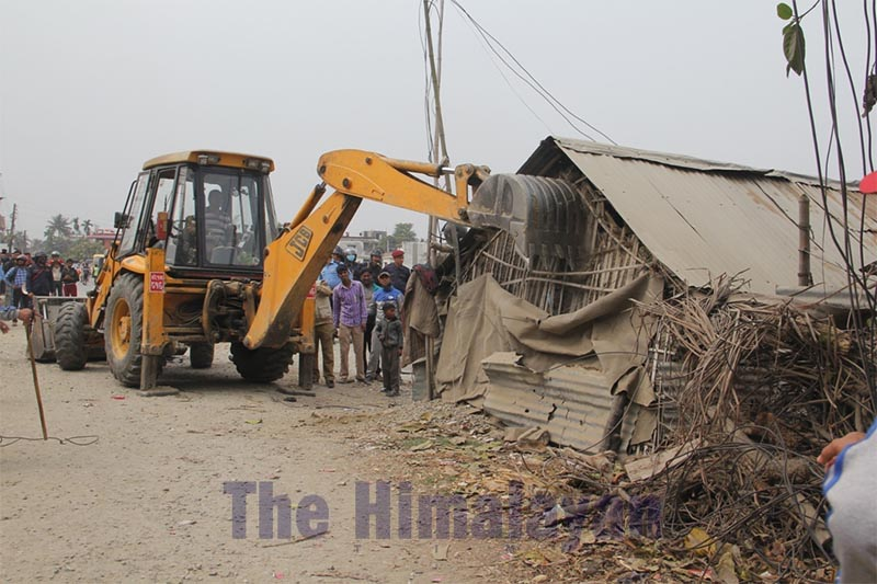 An excavator demolishing a hut that was illegally constructed on the roadside at a squattersu2019 settlement in Biratnagar Metropolitan City, on Tuesday, February 25, 2020. Photo: THT